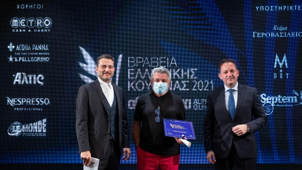 O Αναπληρωτής Υπουργός Εσωτερικών Στέλιος Πέτσας απένειμε το βραβείο στο καλύτερο εστιατόριο ελληνικής κουζίνας στον Λευτέρη Λαζάρου για το Varoulko Seaside. Μαζί τους ο παρουσιαστής της τελετής απονομής των Βραβείων Ελληνικής Κουζίνας 2021 Γιώργος Καραμίχος